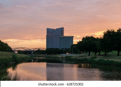 Trinity River Fort Worth, Texas sunrise. Early quiet morning in Trinity Park. Orange, purple and pink colors in the sky. Tall building in the background. Grasses and trees line the river. Horizontal.
