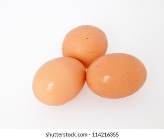 A trio of brown eggs isolated on a white background.