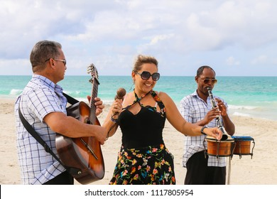 Trio ensemble of musicians consisting of two men and one woman performing on a sandy empty beach, Cuba, Varadero, 31 October 2016