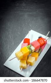 Trio of fresh fruit kebabs with cubes of strawberry, melon, watermelon, kiwifruit, and pineapple on wooden skewers served on a plate, high angle view on slate with copyspace