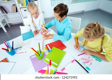 Trio of friends enjoying drawing in an after-school club