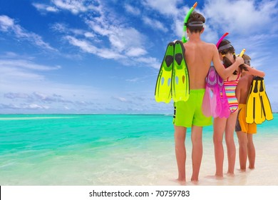 A trio of kids on the beach with fins and snorkels.