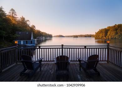 Trio of Muskoka chairs on a patio overlooking Lake Joseph at dawn.