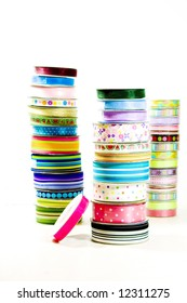 A trio of stacks of brightly colored ribbon on a white background.