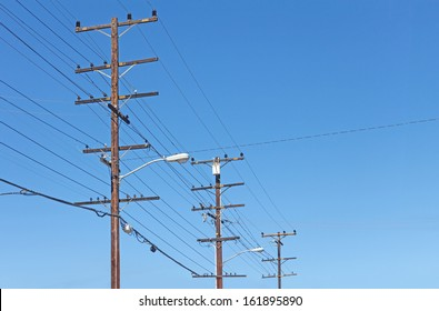 Trio of telephone utility poles, cables, streetlights, and clear blue sky background. Neat rows of parallel distribution wires connected to three tall wood posts. Perspective view.