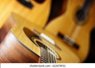 A trio of three acoustic guitars (standard six string in foreground, classical and twelve string behind) are combined to create a music themed image (shallow depth of field on foreground six string)