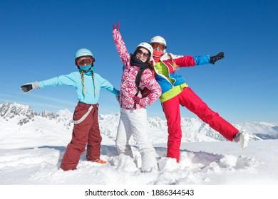 trois jeunes filles en vacances d'hiver dans les montagnes posent dans la neige avec du matériel de ski