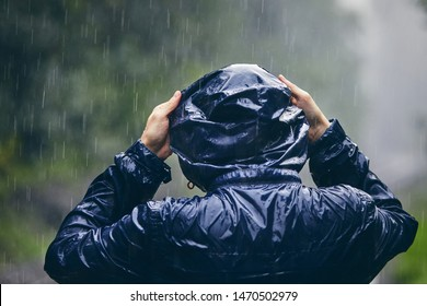Trip in bad weather. Rear view of young man in drenched jacket in heavy rain.