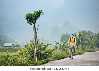 Trip by bike. Man with backpack bicycling on road against karst formation in Ninh Binh province, Vietnam.