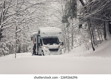 trip with campervan outdoor in the forest wood mountains camper vehicle under the snowflakes in the winter with the road full of snow