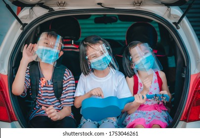 Trip coronavirus protect and social distancing concept, kids playing and singing song on car at home, funny on outdoor stay at home and wearing mask and face shield for protect coronavirus, child thai