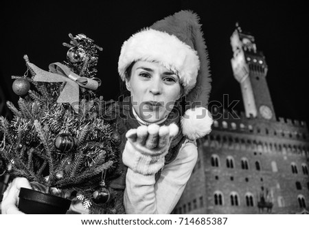 Trip full of inspiration at Christmas time in Florence. happy young woman in Christmas hat in the front of Palazzo Vecchio in Florence, Italy with Christmas tree blowing air kiss