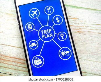 Trip plan words and travel planning icons on blue background on smartphone screen on vintage wooden background. Travel planning concept.