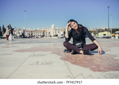 Trip to Portugal and Europe.Traveling to Lisbon.Female turist sitting on a square mosaic map in front of Monument of the Discoveries in Lisbon.Vacation pictures concept.Explore and travel.