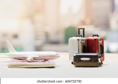 Trip or traveling by airplane concept. Miniature toy airplane on passport and suitcases on vintage map and cityscape background.