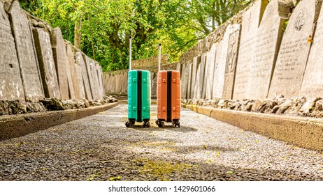 The trip without return, two suitcases on a sidewalk between tombstones in the Abbey Graveyard in the village of Athlone, wonderful sunny day in the county of Westmeath, Ireland