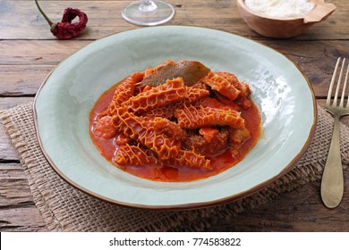 tripe in tomato sauce in a rustic plate on wooden table background