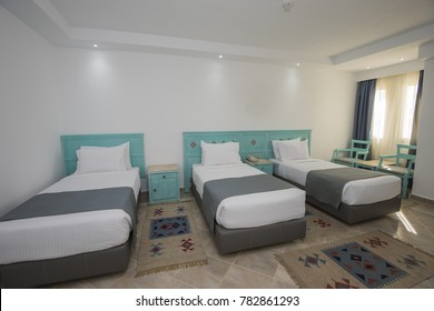 Triple beds in a luxury hotel family room with curtains