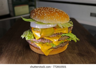 Triple cheeseburger with cheese, lettuce, onion, pickles, Sesame seed bun, Kitchen bacjground.