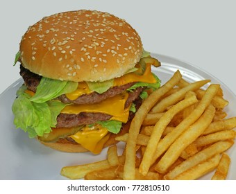 Triple cheeseburger with cheese, lettuce, onion, pickles, Sesame seed bun, french fries. Close crop.