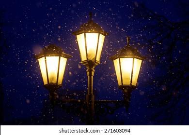 Triple lantern on a dark blue night sky and falling snow