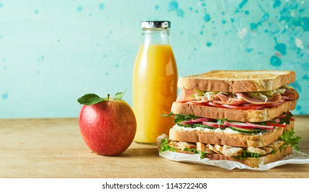 Triple layer meat and vegetable sandwich on white paper with juice and apple on table