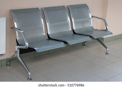 Triple metal chair stands near the wall on the tile floor