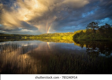 Triple rainbow observed above Jonsvatnet lake near Trondheim, sunset light after stormy day, summer in Norway.