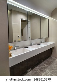 Triple sink in public restroom. Contemporary and luxary interior of public toilet. Clean white basin.