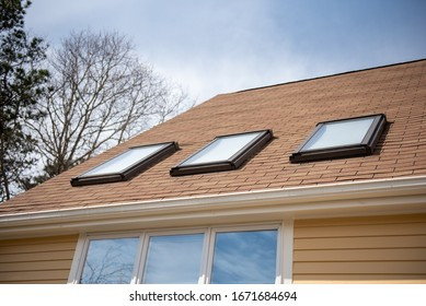 triple skylights on red roof with yellow siding and blue sky with trees in background