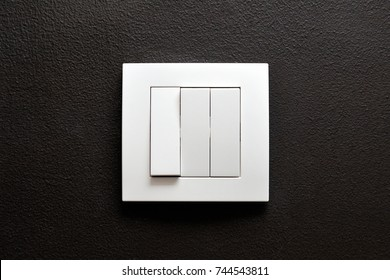 Triple wall light switch on a black wall
