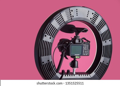 Tripod for camera with round light. In the studio on the pink background. Close-up.