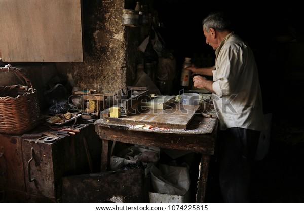 TRIPOLI - NOVEMBER 25: A traditional soap maker in his atelier cutting bars of freshly made soap on 25 November 2017 in Tripoli, Lebanon.