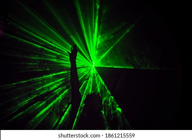 Trippy night image with people dancing outdoors in a forest music festival with laser beams in the background.