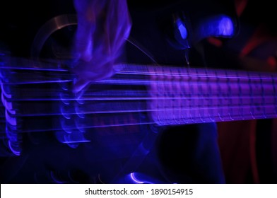 Trippy vibe with Rocck bass guitar player pulling hard on the strings showing movement and playing the guitar live on stage with dim lighting playing music