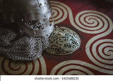 Triskel, Vikings, viking helmet with chain mail on a red shield with golden shapes of sun, weapons for war