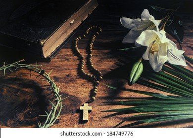 Triumph, Passion, Crucifixion and Resurrection concept.  Iconic symbols relating to Palm Sunday and Easter rest upon a rustic table - Bible, palm branch, crown of thorns, cross, and white lily.