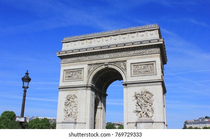 Triumphal Arch (Arc de Triomphe) on Champs Elysees Street and Place Charles de Gaulle Square in Paris, France. Close Up of Famous Tourist Attraction, Travel Landmark of Europe on Sunny Summer Day.