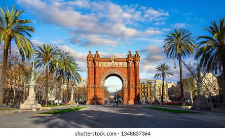 Triumphal Arch in Barcelona, Catalonia, Spain. Arc de Triomf at boulevard street. Alley with tropical palm trees. Early morning landscape with shadows and blue sky with clouds. Famous landmark.