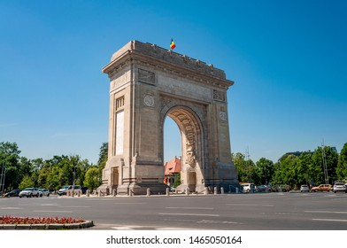 Triumphal Arch, Eastern european landmark and travel destination concept theme with the Arch of Triumph (Arcul de Triumf) in Bucharest (capital city of Romania) against cloudless sky on a summer day