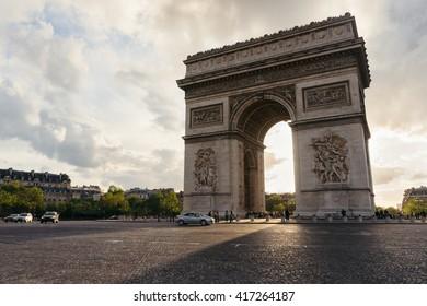Triumphal arch in Paris city at sunset. Arc de Triomphe, Paris landscape, France. Famous Paris view on Triumphal arch. Sunset sun beams through Triumphal arch in Paris. Famous landmark, travel concept