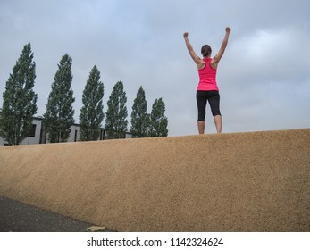 triumphant WOMAN standing IN winning POSE with arms up making fists after workout outdoor at a fitness park