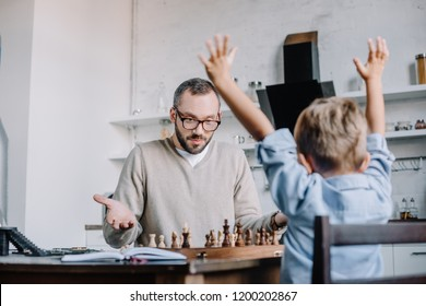triumphing little son raising hands while playing chess with father at home