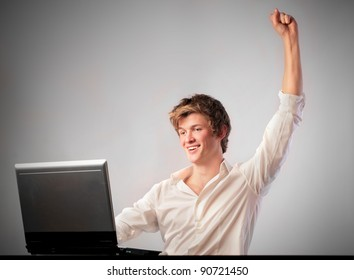 Triumphing young businessman using a laptop