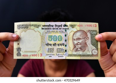 TRIVANDRUM, KERALA, INDIA, AUGUST 15, 2016: Girl holding a Five hundred Rupee Indian Currency note, against black background. Demonetization of Rs 500 Indian currency note.