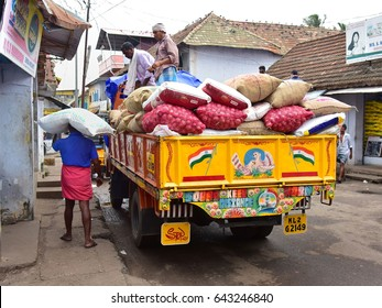 TRIVANDRUM, KERALA, INDIA, AUGUST 22, 2015: Side street of Chalai bazaar where head-load workers unload sackful of rice and onions from a lorry.