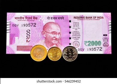 TRIVANDRUM, KERALA, INDIA, JANUARY 01, 2017: Top down view of a new 2000 rupees Indian currency note and three coins on black background.