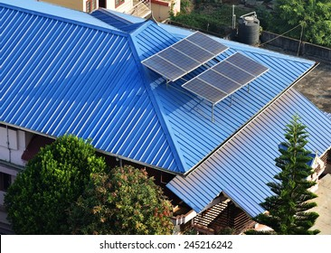 TRIVANDRUM, KERALA, INDIA, JANUARY 17, 2015: Beautiful blue corrugated Aluminium roof of a building showing two rows of solar panels for electricity generation. Geometric shapes. View from above.