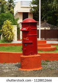 TRIVANDRUM, KERALA, INDIA, JULY 07, 2018: A retro style red post box of India Posts at a road junction in a residential area.