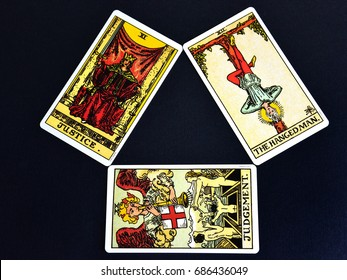 TRIVANDRUM, KERALA, INDIA, JULY 29, 2017: Top down view of tarot cards on black background. Justice, Judgement and the Hanged man. Crime and punishment - conceptual image.